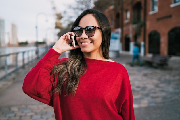 Latijnse vrouw die op de telefoon spreekt.