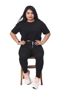 Latijnse vrouw die sportkleding draagt die voorzijde en handen op heup op witte achtergrond zit