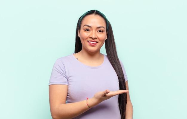 Latijnse vrouw die vrolijk glimlacht, zich gelukkig voelt en een concept in exemplaarruimte met handpalm toont