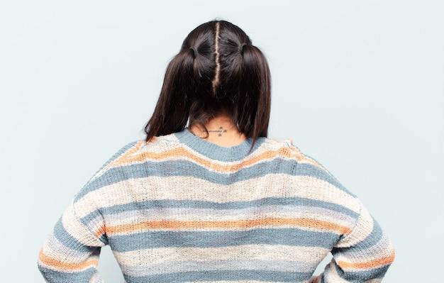 Latijnse vrouw die zich verward of vol voelt of twijfels en vragen, zich afvragend, met de handen op de heupen, achteraanzicht