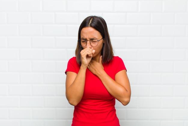 Latijnse vrouw die zich ziek voelt met keelpijn en griepsymptomen, hoesten met bedekte mond