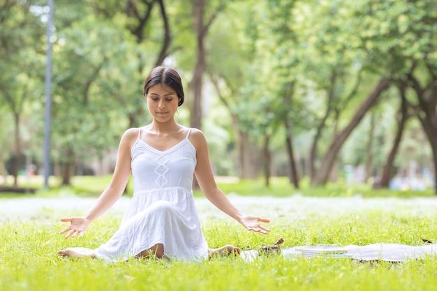 Latijnse vrouw doet meditatie in het park buiten met een tibetaanse kom