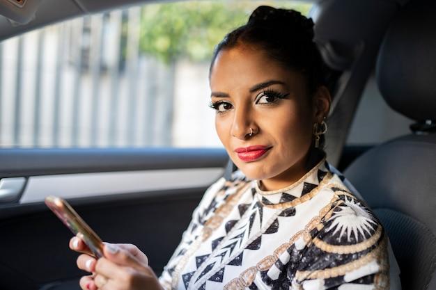 Latijnse vrouw in een auto die haar telefoon gebruikt