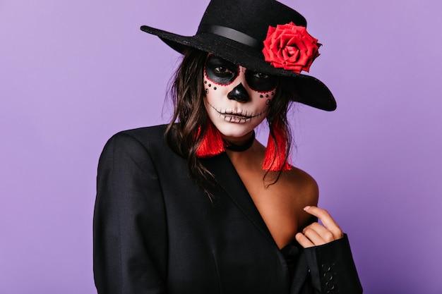 Latijnse vrouw in zwarte jas en sombrero. tevreden meisje in muertosuitrusting die op halloween wacht.