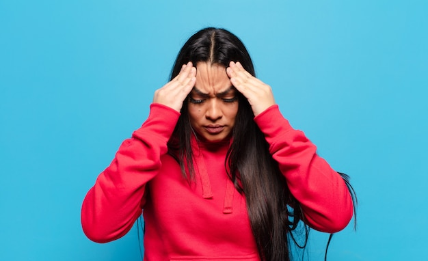Latijnse vrouw kijkt gestrest en gefrustreerd, werkt onder druk met hoofdpijn en heeft problemen