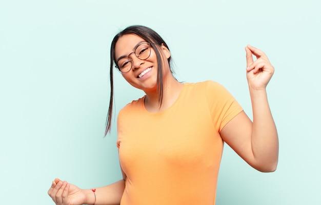Latijnse vrouw lacht, voelt zich zorgeloos, ontspannen en gelukkig, danst en luistert naar muziek, heeft plezier op een feestje