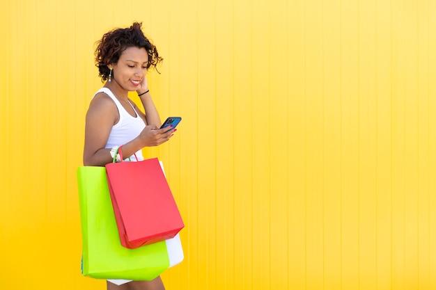 Latijnse vrouw loopt met haar aankoop terwijl ze naar haar smartphone kijkt. gele achtergrond.