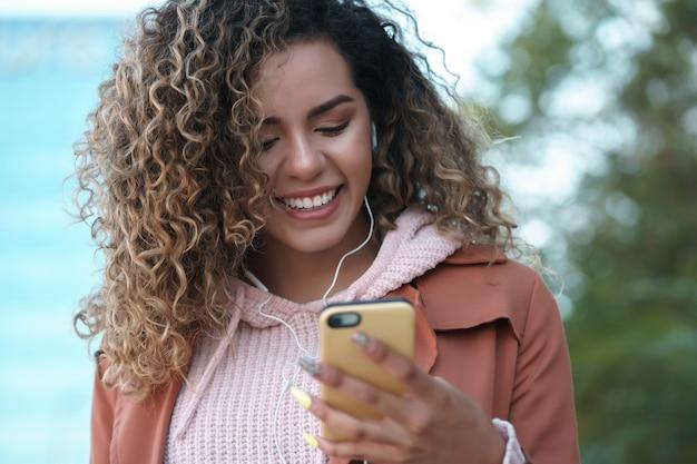 Latijnse vrouw met behulp van haar mobiele telefoon met koptelefoon buitenshuis.