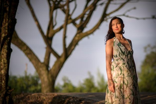 Latijnse vrouw met groene zomerjurk modelleren en glimlachen in het midden van een bos.
