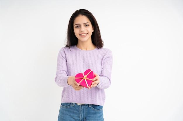 Latijnse vrouw met hartvormige geschenkdoos in handen op witte achtergrond