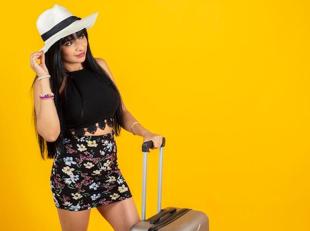 Latijnse vrouw met reiskoffer gele ruimte