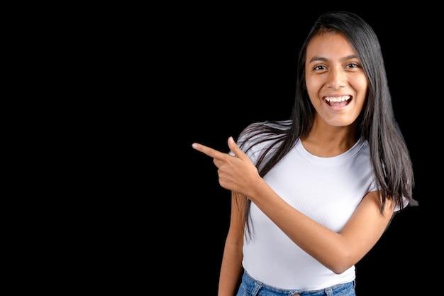 Latijnse vrouw met witte t-shirt op een zwarte achtergrond wijzend met haar wijsvinger en glimlachend