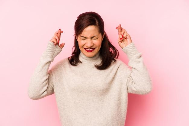 Latijnse vrouw middelbare leeftijd geïsoleerd op roze kruising vingers voor geluk