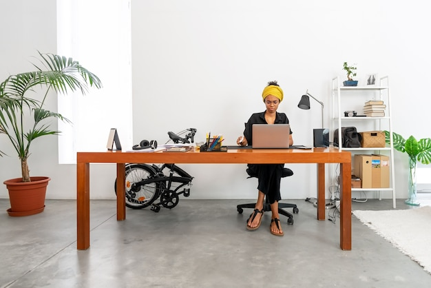 Latijnse vrouw thuis werken met laptop en documenten