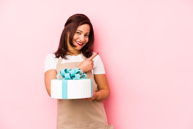 Latijnse vrouw van middelbare leeftijd die een cake houdt die op een roze muur wordt geïsoleerd die en opzij glimlacht richt, die iets op lege ruimte toont.