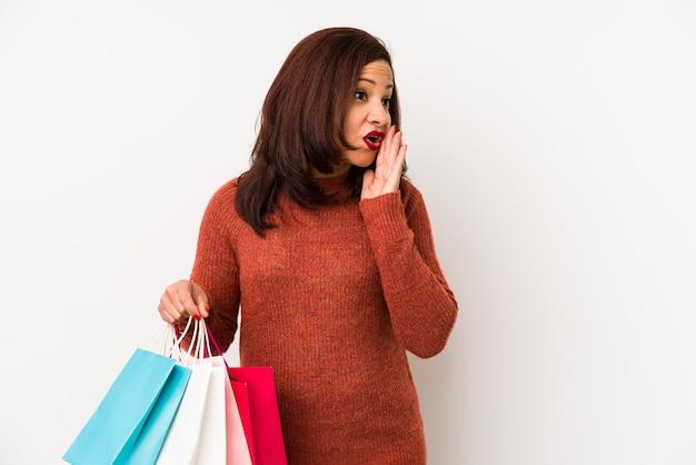Latijnse vrouw van middelbare leeftijd die het winkelen geïsoleerde zakken houdt zegt een geheim heet het remmen nieuws en kijkt opzij