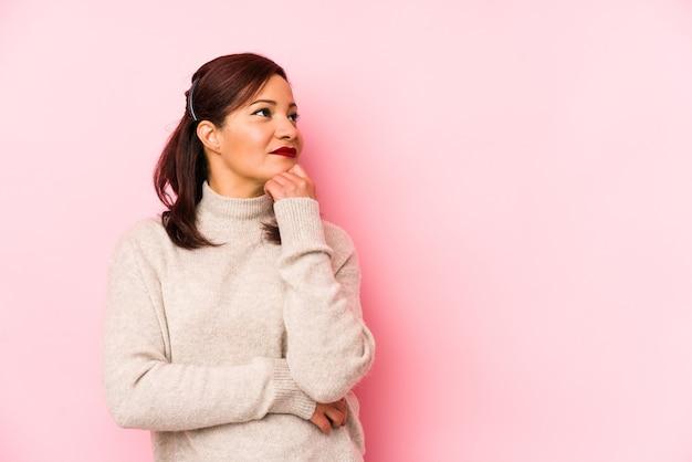 Latijnse vrouw van middelbare leeftijd die op een roze achtergrond wordt geïsoleerd die zijwaarts met twijfelachtige en sceptische uitdrukking kijkt.