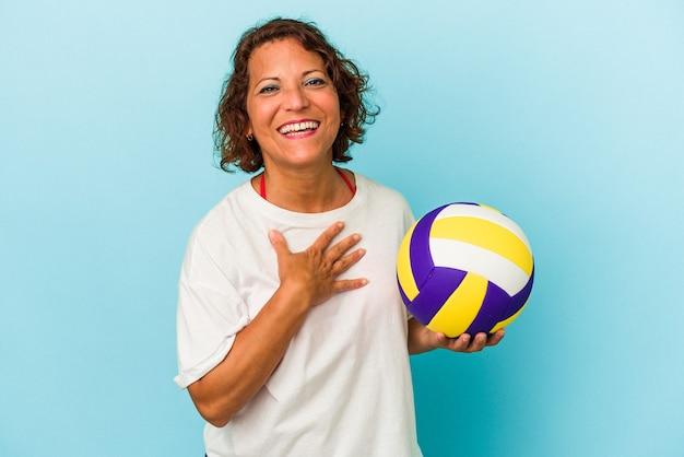 Latijnse vrouw van middelbare leeftijd die volleybal speelt geïsoleerd op blauwe achtergrond lacht hardop terwijl ze de hand op de borst houdt.