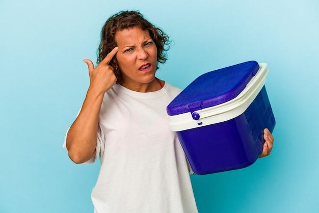 Latijnse vrouw van middelbare leeftijd geïsoleerd op blauwe achtergrond met een gebaar van teleurstelling met wijsvinger.