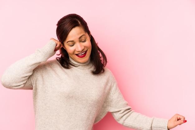 Latijnse vrouw van middelbare leeftijd geïsoleerd op een roze muur dansen en plezier maken.