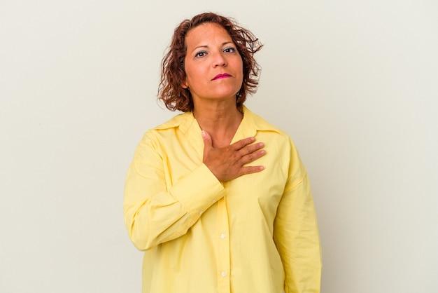 Latijnse vrouw van middelbare leeftijd geïsoleerd op een witte achtergrond die een eed aflegt, hand op de borst.