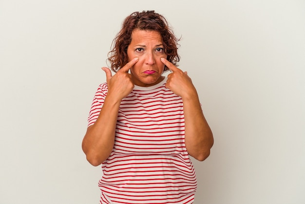 Latijnse vrouw van middelbare leeftijd geïsoleerd op een witte achtergrond huilen, ongelukkig met iets, pijn en verwarring concept.