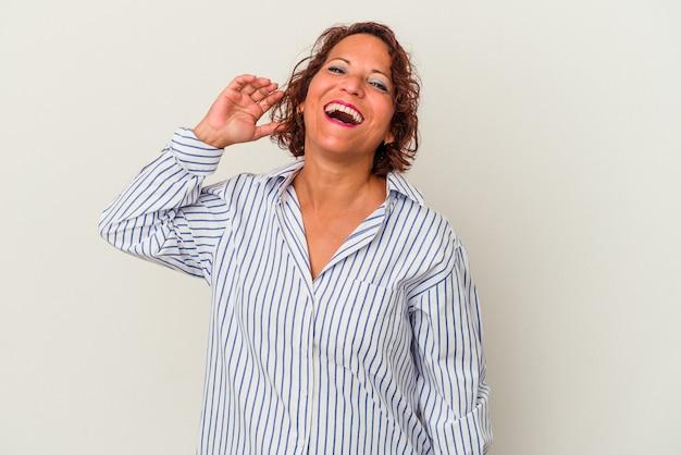 Latijnse vrouw van middelbare leeftijd geïsoleerd op een witte achtergrond lachen om iets, die mond met handen bedekken.