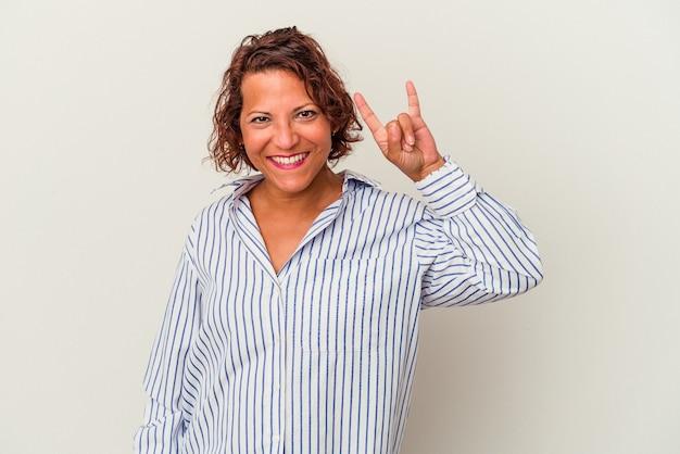 Latijnse vrouw van middelbare leeftijd geïsoleerd op een witte achtergrond met een gebaar van hoorns als een concept van de revolutie.