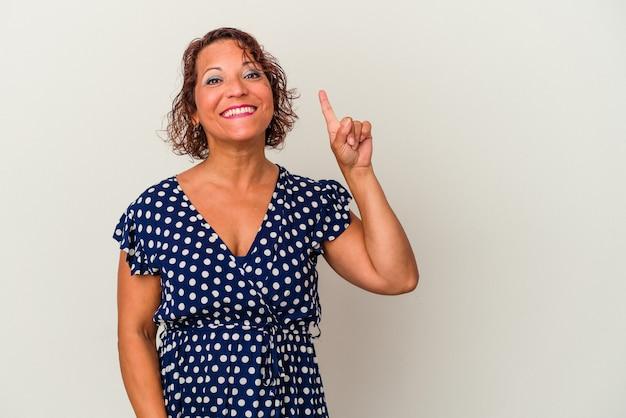 Latijnse vrouw van middelbare leeftijd geïsoleerd op een witte achtergrond met nummer één met vinger.