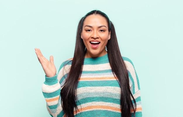 Latijnse vrouw voelt zich blij, verrast en opgewekt, lacht met een positieve houding, realiseert zich een oplossing of idee