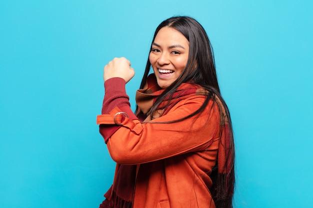 Latijnse vrouw voelt zich gelukkig, tevreden en krachtig, buigt fit en gespierde biceps, ziet er sterk uit na de sportschool