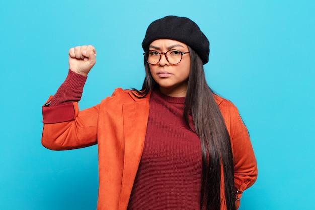 Latijnse vrouw voelt zich serieus, sterk en rebels, steekt haar vuist op, protesteert of vecht voor revolutie