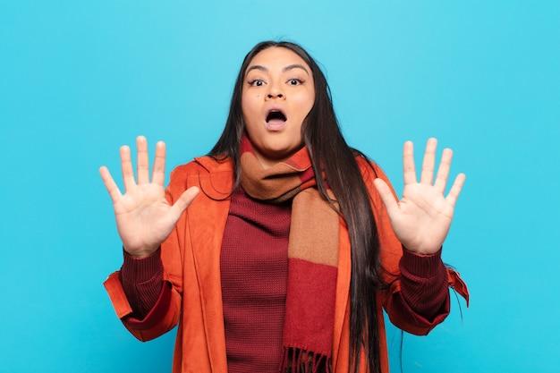Latijnse vrouw voelt zich verdoofd en bang, bang voor iets angstaanjagends, met de handen open vooraan en zegt: blijf weg