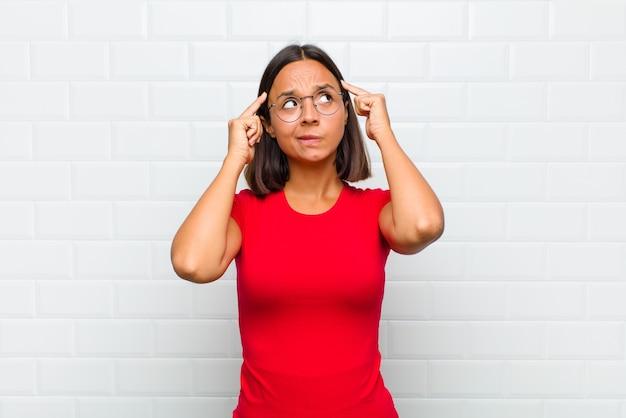 Latijnse vrouw voelt zich verward of twijfelt, concentreert zich op een idee, denkt hard, zoekt ruimte aan de zijkant