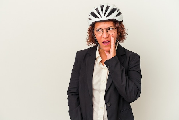 Latijnse zakenvrouw van middelbare leeftijd die een fietshelm draagt die op een witte achtergrond wordt geïsoleerd, zegt een geheim heet remnieuws en kijkt opzij