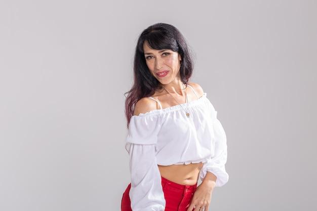 Latina-dans, stripdans, hedendaags en bachata-damesconcept - vrouw die improvisatie danst en haar lange haar beweegt op een witte muur.