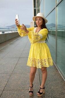 Latina meisje in gele jurk en witte hoed zittend op de grond in de straat.