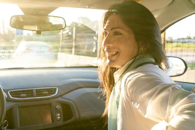 Latina-vrouw die op de passagiersstoel zit terwijl ze met de automobilist praat.