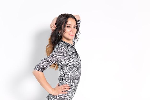Latino dans, improvisatie, eigentijds en mode dansconcept - jonge mooie vrouw die op witte studiomuur danst.