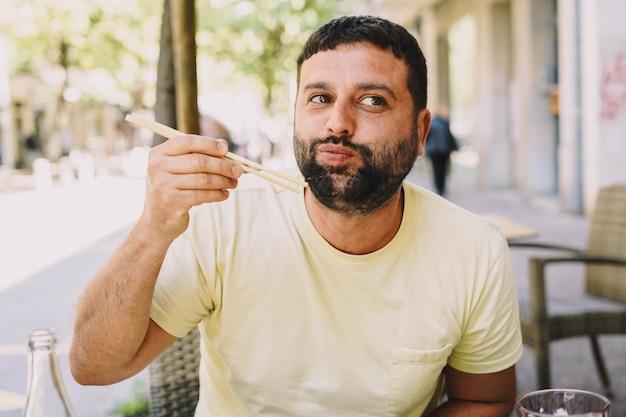 Latino jongen in gele t-shirt die japans eten eet