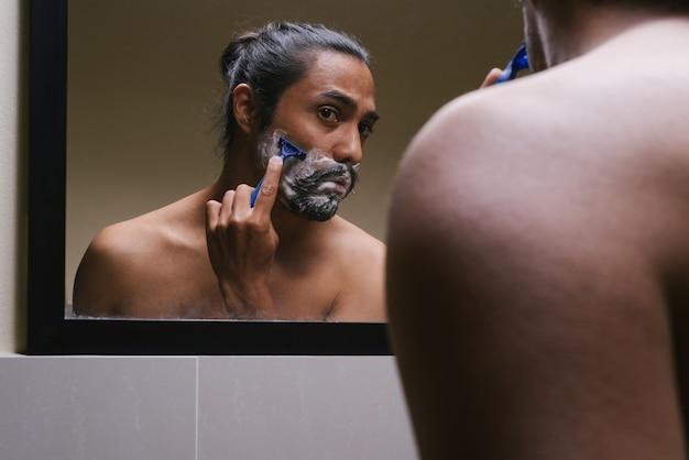 Latino man scheert voor een spiegel met een naakte torso