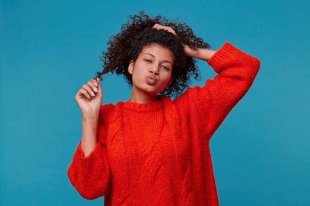 Latino meisje in rode trui met speels flirtend gezicht houdt spelen met haar schattig krullend zwart haar vast en stuurt luchtkus over de blauwe muur
