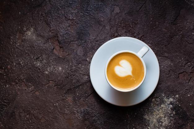 Latte art hart in kopje cappuccino. bovenaanzicht op bruine betonnen achtergrond