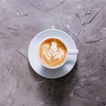 Latte-art in kopje cappuccino. bovenaanzicht op grijze betonnen achtergrond