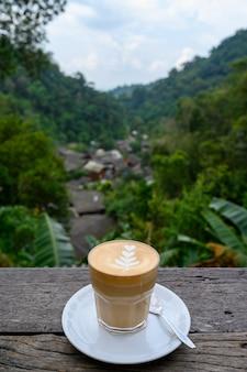 Latte art koffie op houten tafel bij chom nok chom mai in mae kam pong, chiang mai, thailand