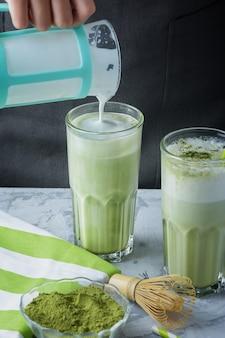 Latte groene matcha. opgeklopte melk wordt toegevoegd aan groene thee. gezond drankje.