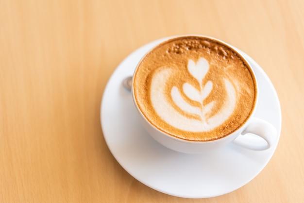 Latte-koffie in glas dat op houten vloer wordt geplaatst.
