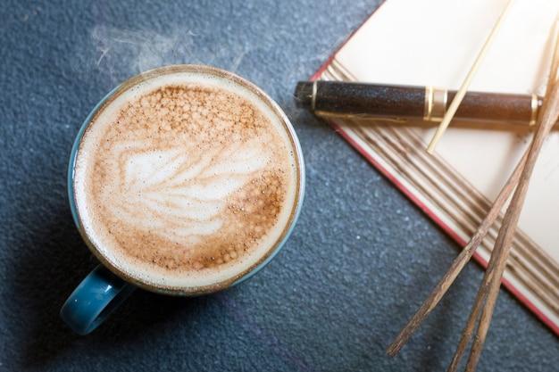 Latte koffiekopje, pen, boek en gedroogde bloemen op houten.