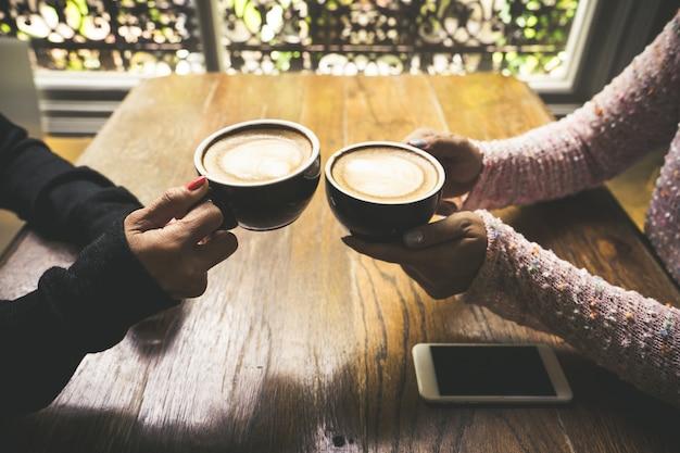 Latte-koffiekunst en mensen die concept van de de koffiewinkel van de vriendschapssamenhorigheid ontmoeten