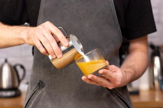Latte-kunst. kunst van het tekenen op koffie. barista maakt latte art-melk van een kruik